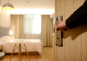 hand on door handle opens door of motel room
