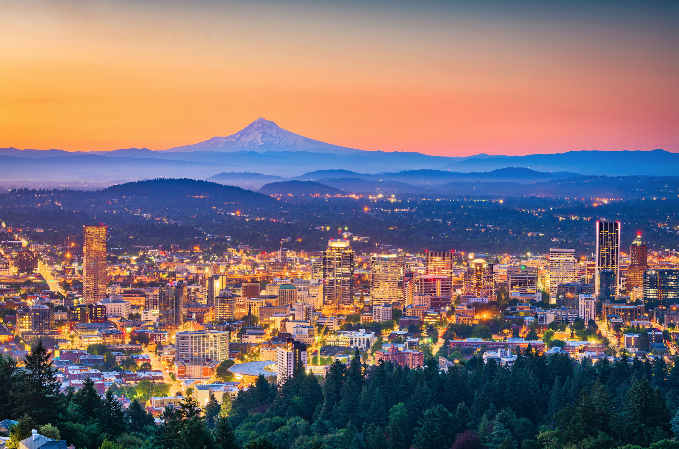 A view of downtown Portland, Oregon lit up by lights at dusk.