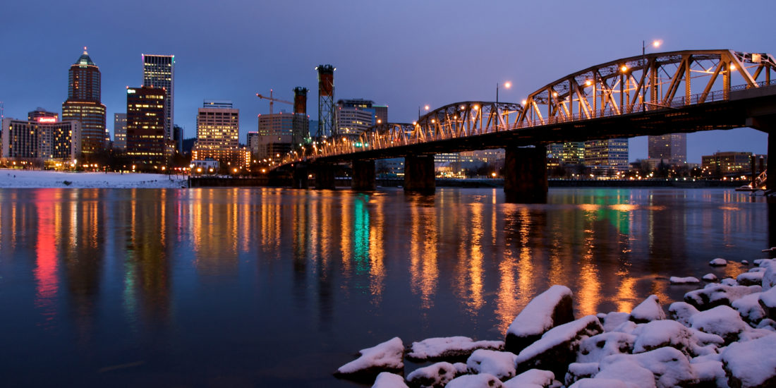 The city lights of Portland Oregon during winter with snow on the ground.